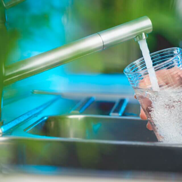 Woman filling a glass of water.